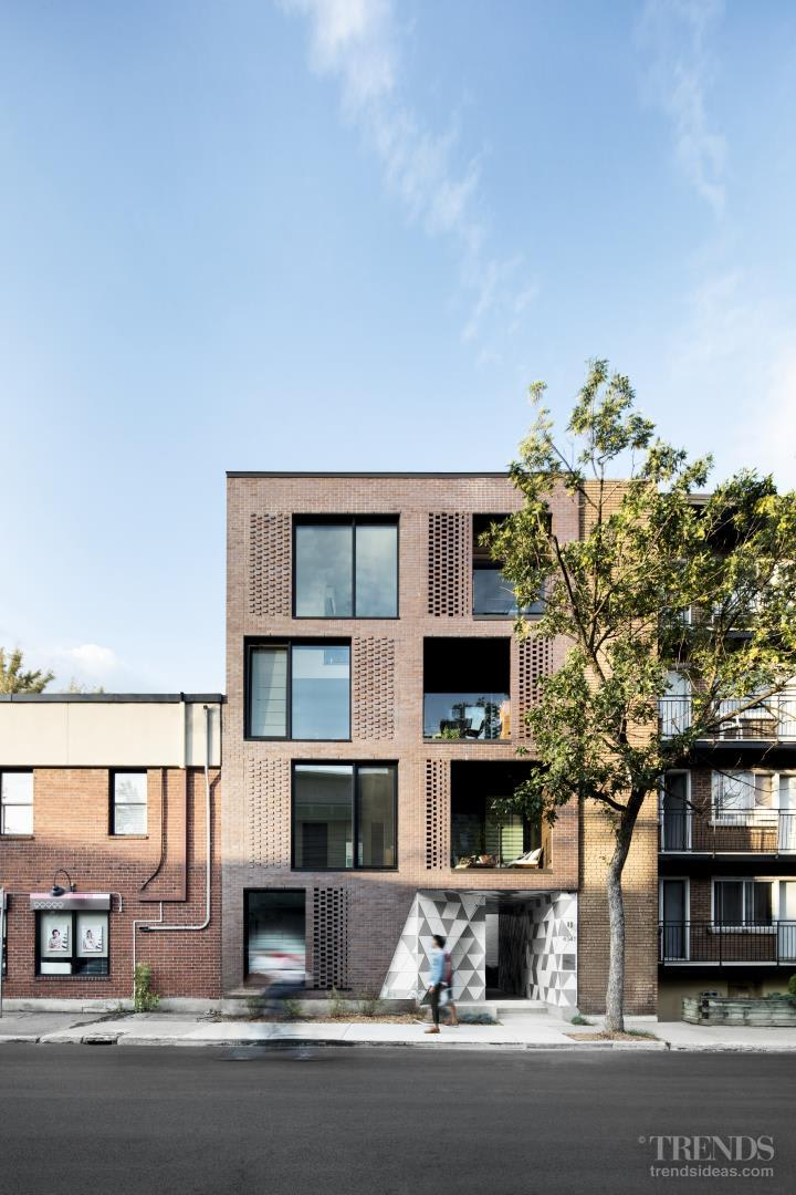 brick apartment building. Rough brick facade fronts an innovative apartment building with a communal  courtyard at its heart