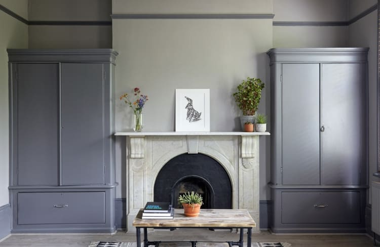 Two large cabinets sandwich the fireplace