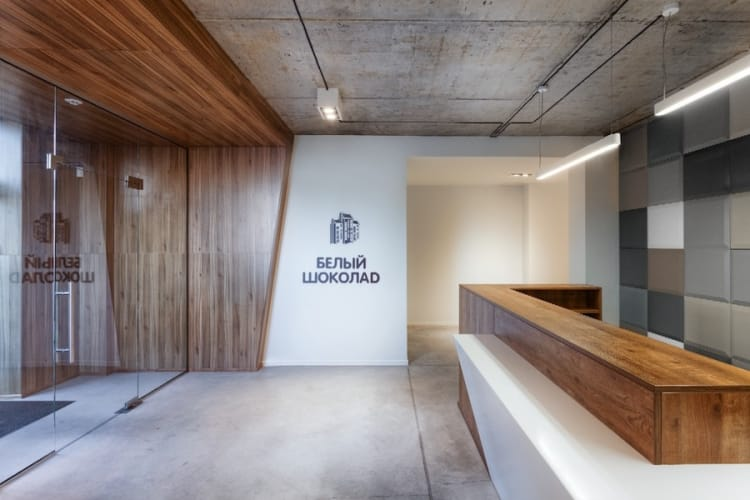 Wood, concrete and glass make up the foyer, with an interesting tile pattern sitting behind the reception desk