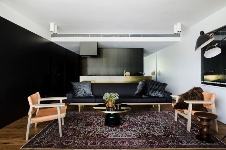 Dark panels give the apartment interior the theatricality and sophistication of a luxury hotel