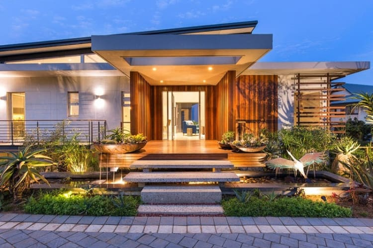 The front entrance uses timber cladding and a variety of plants to create a resort-like feel