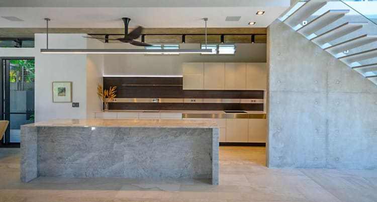 Natural marble and concrete make for complementary surfaces in this modern kitchen by architect David Kane of Pepper Design.