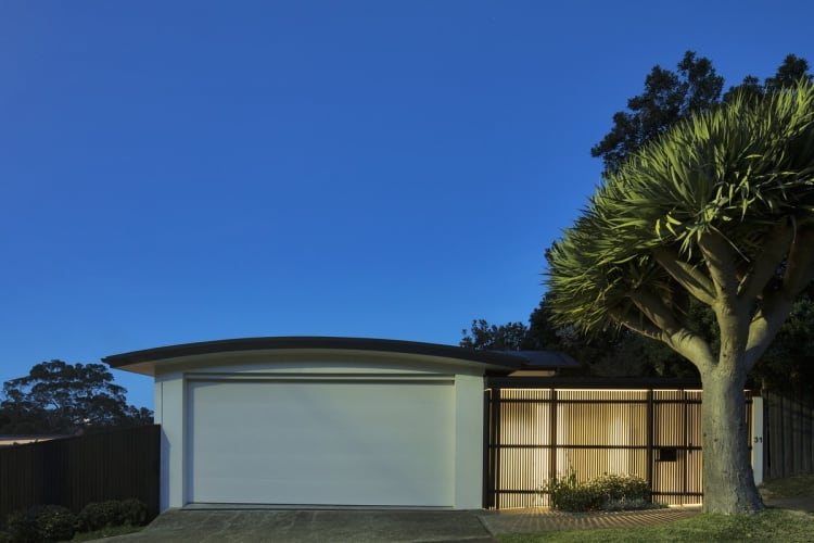 The home presents a clean facade to the street, with a garage with an arced roof and simple fence