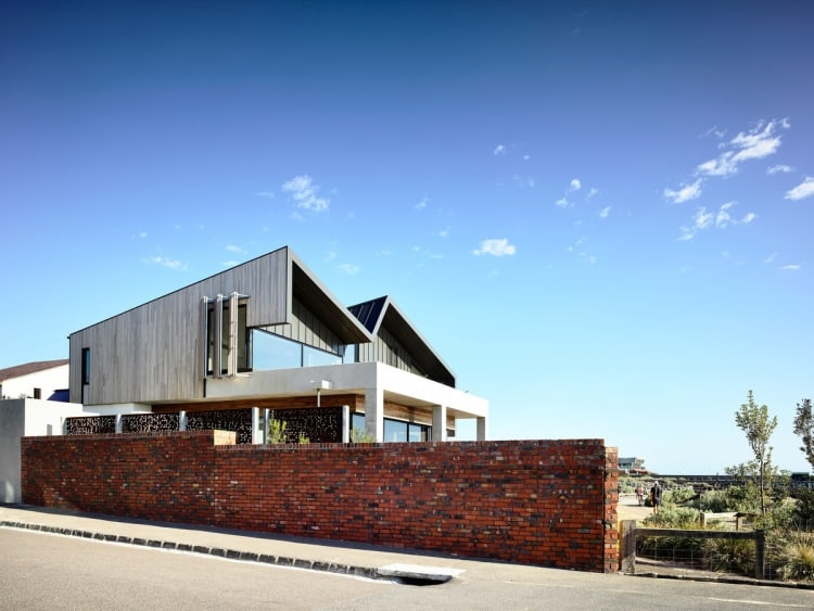 Off form concrete, timber cladding and brick masonry feature throughout this home