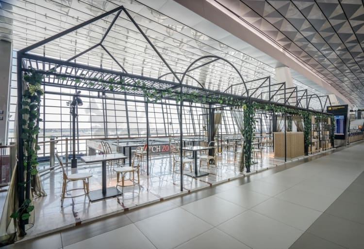 Subtle green touches create a greenhouse-like aesthetic inside the airport