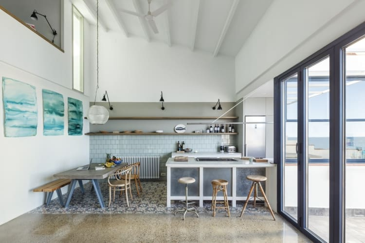 An updated, communal kitchen features both a dining table and an island