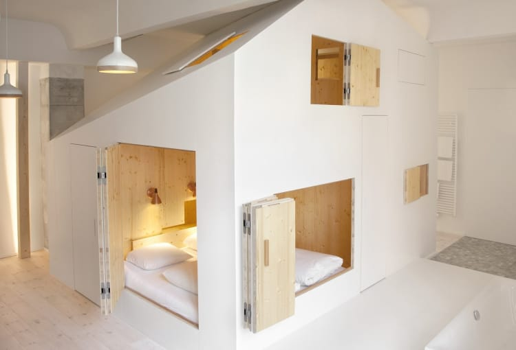 This hotel room contains a tiny house with a bed
