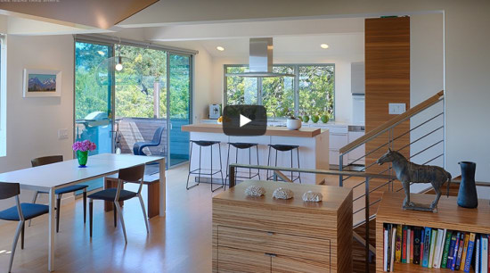 Modest, open-plan family kitchen with walnut cabinetry, central island and oak floors