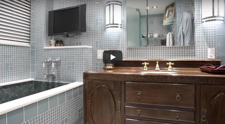 Bathroom remodel incorporating components of Art Deco style through use of tiles and light fixtures
