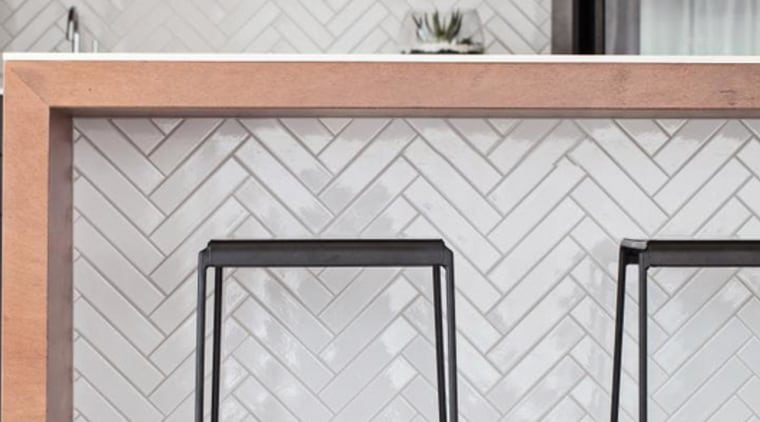 Piece by piece – the matching herringbone tiles on the island and rear breakfast bar of this kitchen were all applied individually by hand