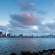 Manhattan's skyline expands with the new editions. architecture, building, city, cityscape, cloud, daytime, downtown, horizon, human settlement, landmark, metropolis, metropolitan area, mountain, ocean, photography, river, sea, sky, skyline, skyscraper, tower block, tree, urban area, water, teal
