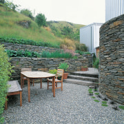 Outdoor dining furniture in courtyard, surrounded by schist backyard, garden, grass, landscape, outdoor structure, plant, stone wall, walkway, wall, yard, white