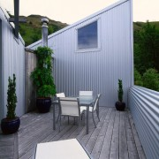 Wooden deck with outdoor table and chairs, enclosed architecture, backyard, facade, home, house, outdoor structure, real estate, roof, siding, yard, gray