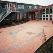 Courtyard at Te Wananga o Aotearoa, showing faded brick, brickwork, concrete, courtyard, driveway, floor, house, outdoor structure, real estate, residential area, road surface, walkway, wall, black
