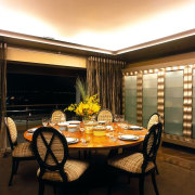 The dining area of this well-designed home - ceiling, conference hall, dining room, interior design, restaurant, room, table, black, brown