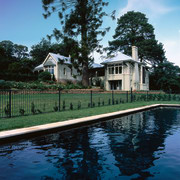 The view of a house overlooing a pool architecture, cottage, estate, home, house, lake, mansion, outdoor structure, plant, property, real estate, reflection, sky, swimming pool, tree, villa, water, waterway, black