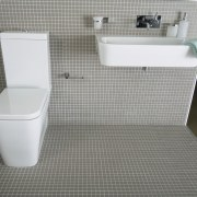 view of the bathroom featuring tiled walls, kohler bathroom, bidet, ceramic, floor, flooring, plumbing fixture, product, product design, tile, toilet, toilet seat, gray