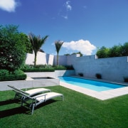 This rectangular pool is screened by concrete plaster architecture, backyard, estate, grass, hacienda, house, landscape, landscaping, lawn, leisure, outdoor furniture, plant, property, real estate, residential area, sky, sunlounger, swimming pool, villa, yard, blue