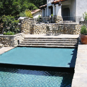 View of swimming pool featuring automatic pool cover, backyard, leisure, outdoor furniture, outdoor structure, property, sunlounger, swimming pool, water, white, black