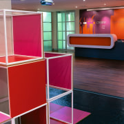Bold blocks of vibrant colour are stationed in display case, furniture, glass, interior design, product design, shelf, shelving, table, red