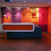 The reception desk  has a feature wall ceiling, floor, furniture, interior design, lighting, orange, recreation room, table, wall, red