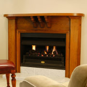 Black gas fireplace set in wooden surround, with fireplace, furniture, hearth, wood burning stove, orange, brown