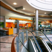 Glass balustrades with timber railings permit views to interior design, lobby, shopping mall, gray