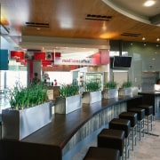 Grasses in stainless steel containers and furniture demarcate cafeteria, food court, interior design, restaurant, black