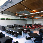 This multi functional space can be used by auditorium, ceiling, classroom, conference hall, institution, interior design, table, gray, brown