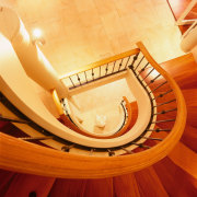 Large curved staircase with wooden steps linking three ceiling, floor, flooring, hardwood, orange, product design, wood, orange