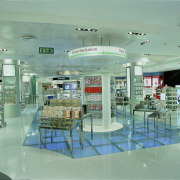 The cosmetics and beauty products are on a glass, interior design, retail, shopping mall, green