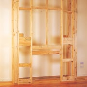 Timber framing for installing a gas fireplace against bookcase, cabinetry, cupboard, floor, furniture, hardwood, lumber, plywood, shelf, shelving, wall, wardrobe, wood, wood stain, orange