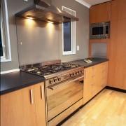 Kitchen with wooden cabinetry and black benchtop, stainless cabinetry, countertop, cuisine classique, floor, flooring, hardwood, interior design, kitchen, room, wood, wood flooring, orange