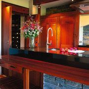 The view of a kitchen island with the countertop, furniture, interior design, kitchen, lighting, room, table, red
