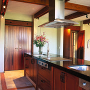 The view of the central island of a cabinetry, ceiling, countertop, flooring, hardwood, home, interior design, kitchen, real estate, room, wood, red