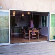 Glass foldback doors open wide providing flow from door, floor, house, outdoor structure, patio, porch, window, white, gray