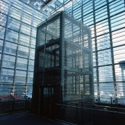 This glass-panelled lift carries passengers from the transport architecture, building, corporate headquarters, daylighting, facade, glass, metropolis, metropolitan area, skyscraper, structure, window, black, teal