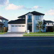 Frontal view of this double-storey home - Frontal architecture, asphalt, building, elevation, estate, facade, home, house, neighbourhood, property, real estate, residential area, roof, siding, sky, suburb, blue
