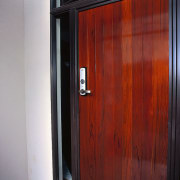 A photograph of a wooden door with a door, wardrobe, wood, wood stain, red, gray