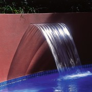 A photograph featuring a red wall with a light, lighting, reflection, water, water feature, water resources, black, red
