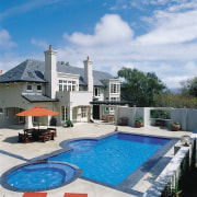 A view of the back of this large estate, home, house, leisure, property, real estate, sky, swimming pool, villa, white, teal
