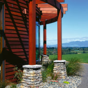 A photograph of kiwi schist columns. There is house, outdoor structure, sky, walkway, wood, red