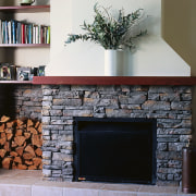 A fireplace with a stone surround. The area fireplace, hearth, wood burning stove, black, gray