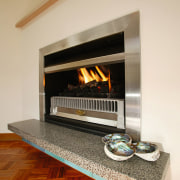 A fireplace with a stainless steel surround. The fireplace, floor, flooring, hearth, heat, wood burning stove, orange, brown