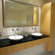 A bathroom featuring a large mirror, basins, taps bathroom, bathroom accessory, bathroom cabinet, countertop, interior design, plumbing fixture, product design, room, sink, brown