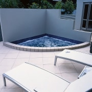 A small cornered spa pool. The area also angle, chair, daylighting, floor, furniture, glass, outdoor furniture, product, sunlounger, swimming pool, table, white, blue