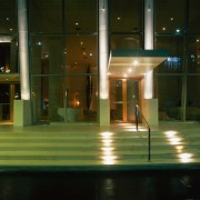 View of the front entrance to this hotel architecture, glass, house, light, lighting, night, reflection, window, black, brown