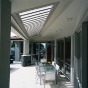 An outdoor sitting area featuring an aluminium opening ceiling, daylighting, interior design, real estate, roof, window, gray, black