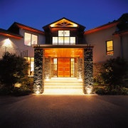 View of the lakehouse's entrance way. Features two architecture, building, estate, evening, facade, home, house, landscape lighting, lighting, mansion, night, property, real estate, residential area, sky, window, black