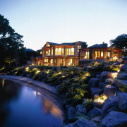 Side on view of lakeside property. Features rock architecture, estate, evening, home, house, landscape, landscape lighting, lighting, mansion, morning, night, property, real estate, reflection, residential area, resort, sky, tree, villa, water, white, black
